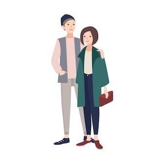 Para młody mężczyzna i kobieta ubrani w stylowe nowoczesne ubrania stojąc razem, uśmiechając się i obejmując. modna para. postaci z kreskówek na białym tle. ilustracja wektorowa płaski.