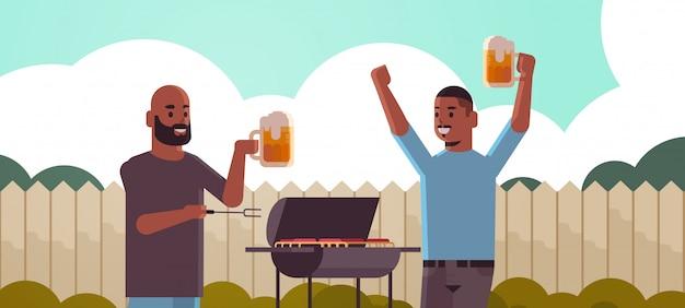 Para młodych facetów przygotowywanie mięsa na grillu afroamerykanie picie piwa przyjaciele zabawy piknik na podwórku grill party koncepcja płaski portret poziomy