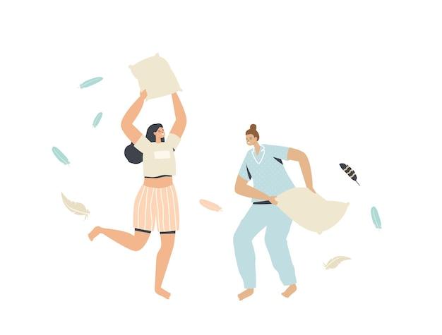 Para młodych kobiet w piżamach walczy w domu na poduszki z latającymi piórami