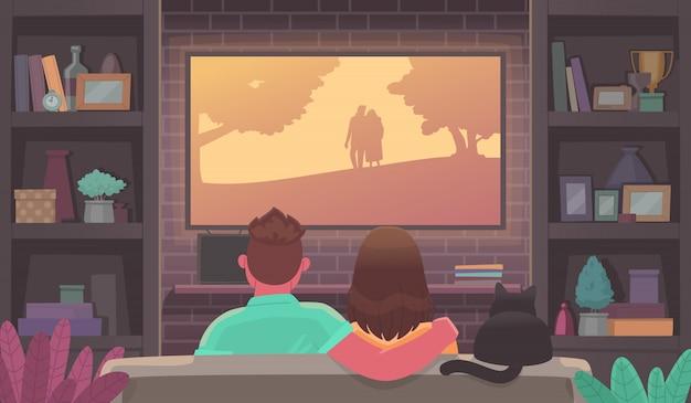 Para młodych ludzi ogląda telewizję. mężczyzna i kobieta w przytulnej atmosferze oglądają film. zostań w domu. reklama usługi przesyłania strumieniowego lub kina online.
