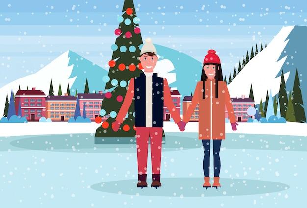 Para na łyżwach w lodowisku z choinką w hotelu w ośrodku narciarskim