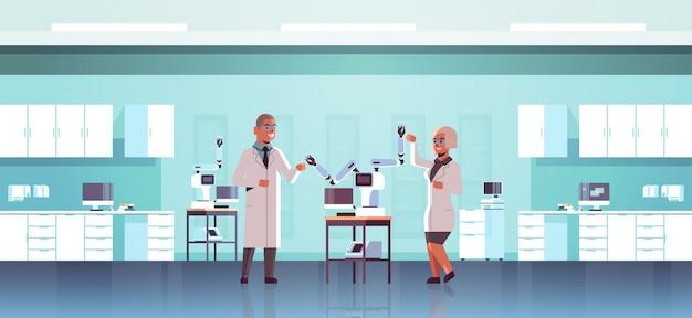 Para naukowców w pobliżu przemysłowych robotycznych ramion