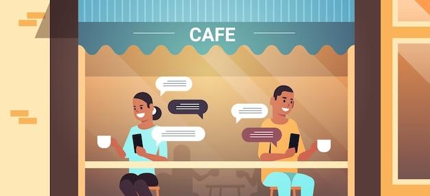 Para odwiedzających pije kawę za pomocą czatującej aplikacji mobilnej na smartfonie w sieci społecznościowej czat bańka komunikacji
