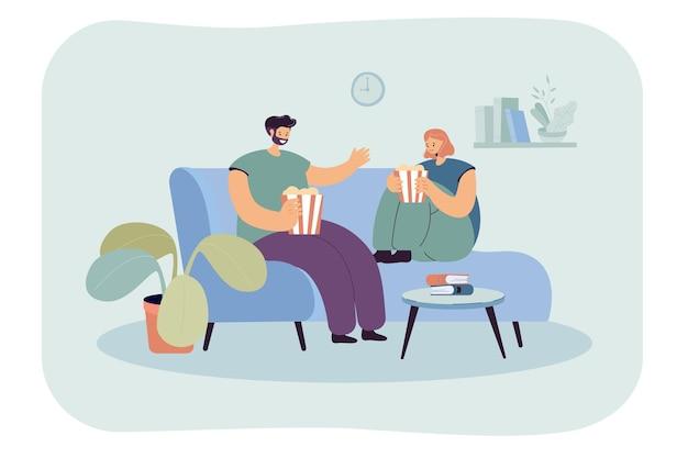 Para relaksuje się na wygodnej kanapie przed telewizorem