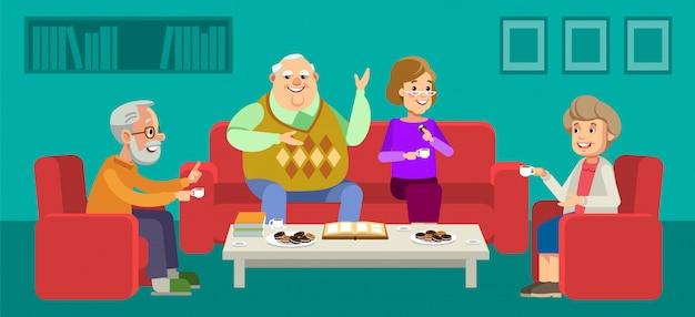 Para seniorów cieszy rozmowę z gośćmi przy filiżance kawy w domu.