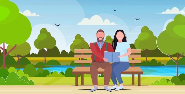 Para siedzi na drewnianej ławce, czytanie książki nadwagą mężczyzna kobieta