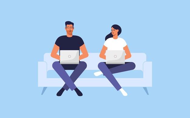 Para siedzi na kanapie z laptopami