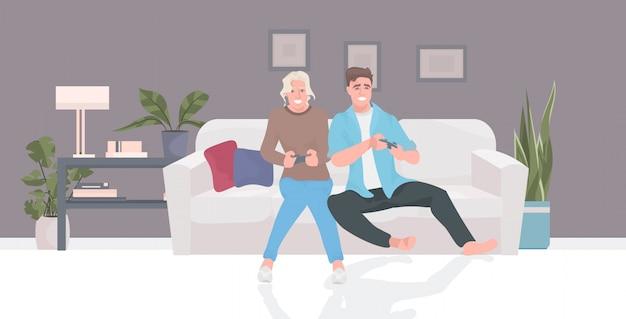 Para siedzi na kanapie za pomocą joysticka kobieta mężczyzna grając razem w gry wideo podczas pandemii koronawirusa