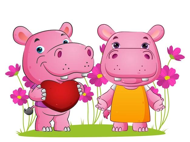 Para słodkich hipopotamów trzyma miłość i stoi z ilustracją szczęśliwej twarzy