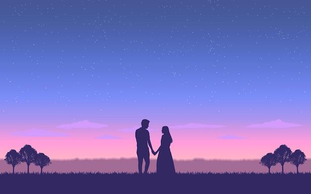 Para sylwetka trzymając rękę razem pod wieczornym niebem
