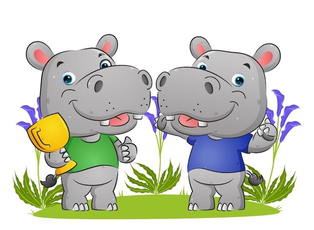 Para szczęśliwych zwycięzców hipopotamów trzyma trofeum i robi ilustrację uroczystości