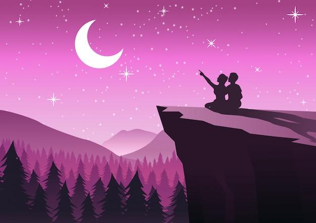 Para wskazując na księżyc w nocy