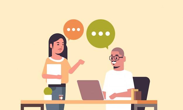 Para współpracowników biznesowych za pomocą laptopa w miejscu pracy biurko czat bańki komunikacji biznesmeni omawianie nowego projektu podczas spotkania