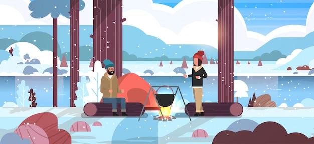 Para wycieczkowicze mężczyzna kobieta gotowania posiłki w meloniku wrzenia garnek na ognisko namiot camping koncepcja zima krajobraz natura rzeka śnieg