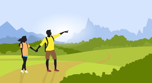 Para wycieczkuje mężczyzna kobiety sylwetki podróżnika górę
