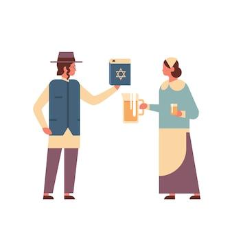 Para żydów trzymająca księgę biblijną i dzban żydówka kobieta w tradycyjnych strojach stojąca razem szczęśliwe święta chanukowe judaizm