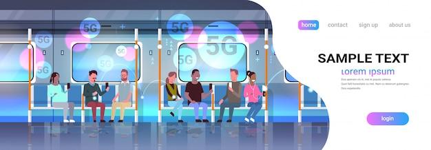 Pasażerowie metra korzystający ze smartfonów online bezprzewodowy system połączenie nowoczesne miasto transport publiczny metro podziemny tramwaj wnętrze horyzontalne pełnej długości kopia przestrzeń