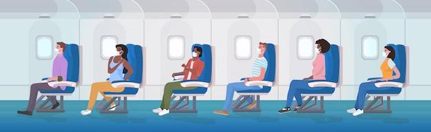 Pasażerowie samolotów noszący medyczne maski na twarz zapobiegające pandemii covid-19 przez koronawirusa