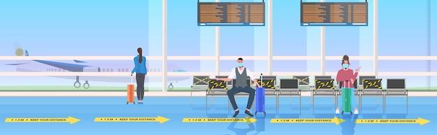Pasażerowie zachowują odległość, aby zapobiec koncepcji dystansowania społecznego koronawirusa wnętrze terminala lotniczego