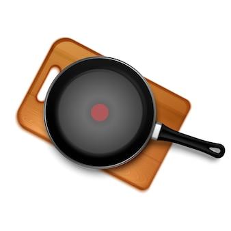 Patelnia teflonowa z czerwonym wskaźnikiem na drewnianej desce na białym tle widok z góry