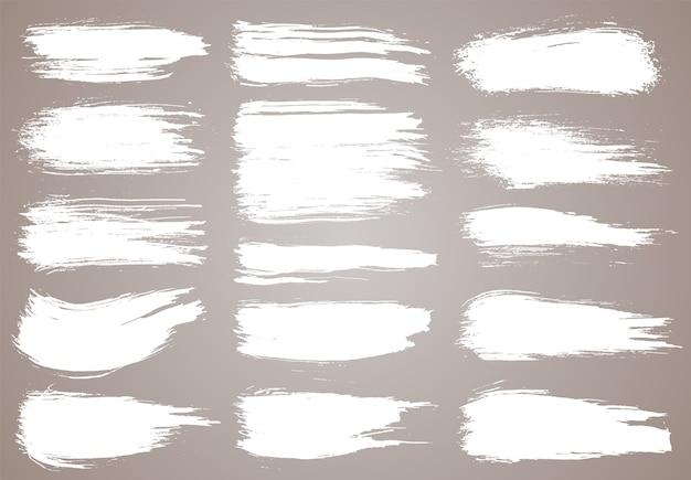 Pędzel malarski. pociągnięcia pędzlem grunge biały atrament. elementy projektu grunge. malowane paski atramentu.