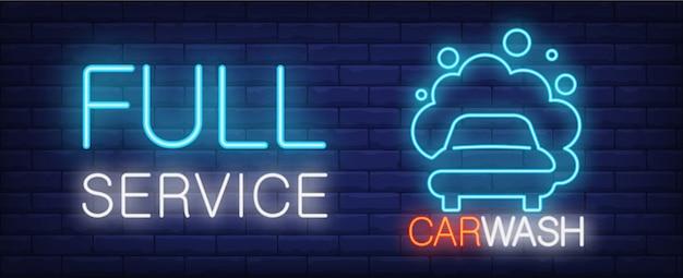Pełny serwis myjnia neon znak. pojazd w piance i świetlistym napisem na ścianie z cegły.