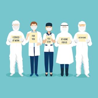 Personel medyczny, lekarz, pielęgniarka i pracownik w szpitalu trzymają papierową tabliczkę, aby nakłonić ludzi do pozostania w domu podczas epidemii wirusa pandemii covid-19, by przestał się rozprzestrzeniać