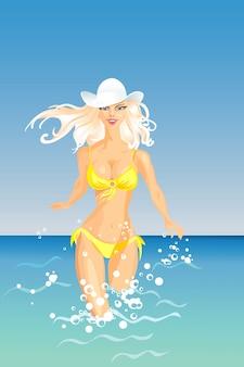 Piękna blond dziewczyna z długimi włosami w białym kapeluszu i żółtym kostiumie kąpielowym wchodzi do morza