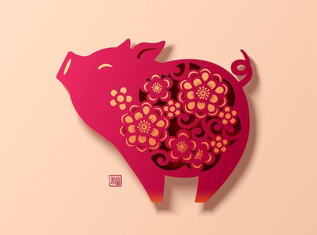Piękna chińska świnka wycięta z papieru z kwiatami na ciele, słowo szczęścia napisane chińskim znakiem obok świni