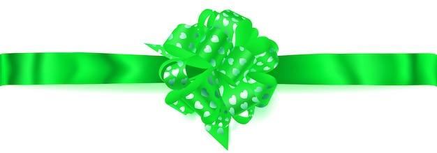 Piękna duża pozioma kokardka wykonana z zielonej wstążki z małymi błyszczącymi serduszkami z cieniem na białym tle