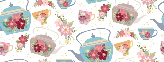 Piękna filiżanka i czajnik z kwiatem i liśćmi odizolowywającymi na bielu