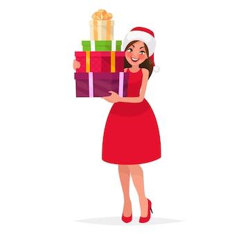 Piękna kobieta ubrana w świąteczny kapelusz i czerwoną sukienkę trzyma prezenty