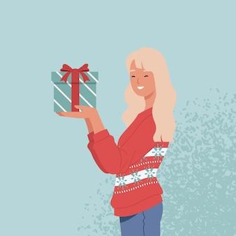 Piękna kobieta w swetrze trzyma prezent na boże narodzenie w dłoniach. ilustracja w stylu płaskiej