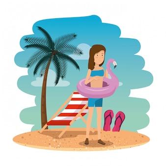 Piękna kobieta z flamandzkim pływakiem na plażowej scenie