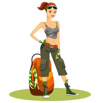 Piękna młoda kobieta z plecakiem w typowych modnych strojach turystycznych