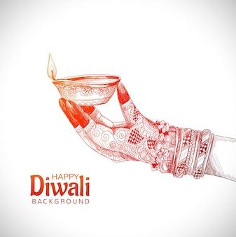 Piękna ręka trzyma szkic na tle festiwalu indyjskiej lampy naftowej diwali