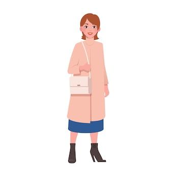 Piękna uśmiechnięta młoda kobieta w modnym płaszczu z torbą