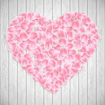Piękne serduszko wykonane z różowych płatków sakury na drewnianej fakturze.