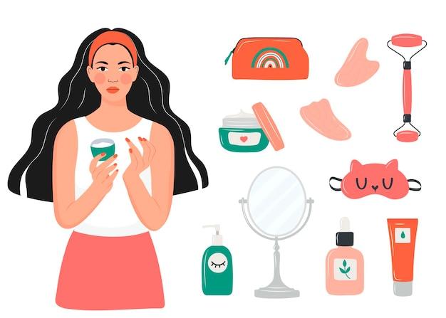 Pielęgnacja twarzy. dziewczyna smaruje twarz kremem. zestaw masażerów i kremów do twarzy. masaż z qua
