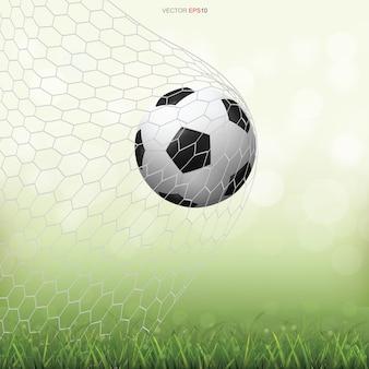 Piłka nożna piłka na zielonej trawie z jasnym niewyraźne tło bokeh