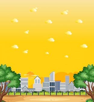 Pionowa scena natury lub krajobraz wiejski z widokiem na miasto i żółtym widokiem na niebo o zachodzie słońca