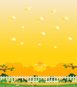 Pionowa scena przyrody lub krajobraz wiejski z częścią ogrodzenia w widoku gospodarstwa i żółtym widokiem na niebo zachód słońca