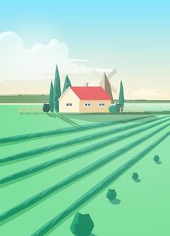 Pionowy krajobraz wsi z budynkiem rolniczym i zaoranym zielonym polem przeciw wiatrakowi i niebu z chmurami