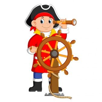 Piraci trzymają lornetkę i sterują statkiem