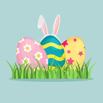 Pisanki i króliczek w trawie. królicze uszy. kolorowe jajka o różnych fakturach, wzorach i kolorach. ferie wiosenne. ilustracja wektorowa na białym tle na niebieskim tle
