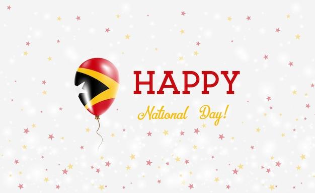 Plakat patriotyczny z okazji święta narodowego timoru wschodniego. latający balon gumowy w kolorach flagi timoru wschodniego. tło święto narodowe timoru wschodniego z balonem, konfetti, gwiazdy, bokeh i błyszczy.