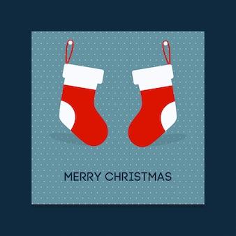 Plakat świąteczny. wesołych świąt. szczęśliwego nowego roku. bożenarodzeniowe skarpety wiesza na ścianie. niebieskie tło