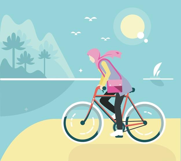 Płaska rowerowa dziewczyna z hijab przy plażą