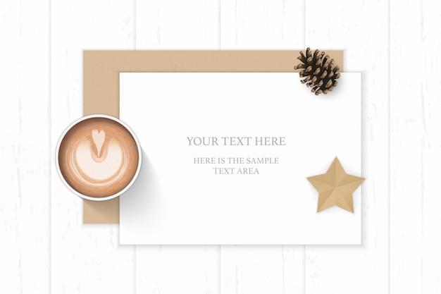 Płaski leżał widok z góry elegancka biała kompozycja koperty z papieru pakowego szyszka kawa i rzemiosło w kształcie gwiazdy na drewnianym tle.