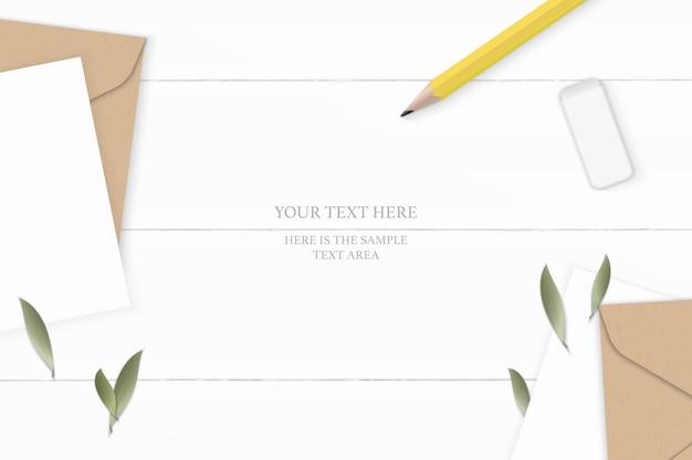 Płaski świecki widok z góry elegancka biała kompozycja listu koperta z papieru pakowego liść żółty gumka do ołówka na drewnianym tle.